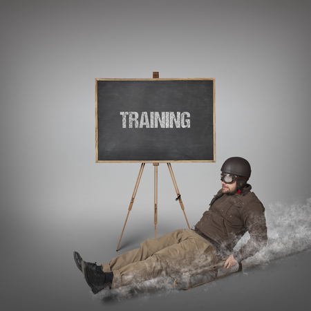 sledging people: Training text on blackboard with businessman sliding with a sledge Stock Photo
