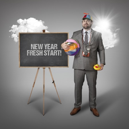 fresh start: New year fresh start text with holiday gear businessman and blackboard with text