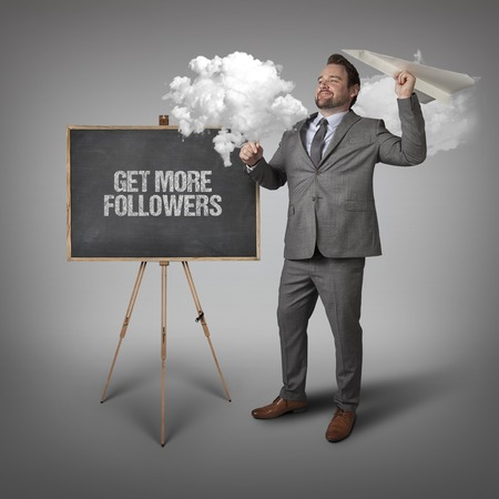 admirers: Get more followers text on blackboard with businessman and paper plane Stock Photo
