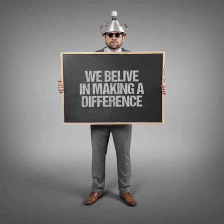 belive: We belive in making a difference text on blackboard with science businessman holding blackboard sign
