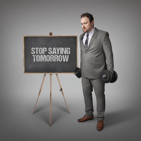 exclaiming: Stop saying tomorrow  text on blackboard with businesssman holding weights Stock Photo