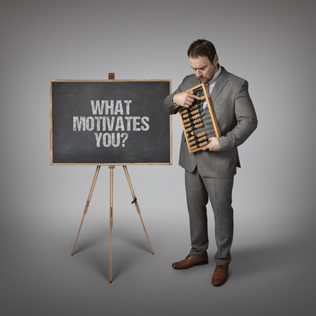 persuades: What motivates you  text on blackboard with businessman and abacus