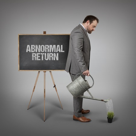 abnormal: Abnormal return text on  blackboard with businessman watering plant