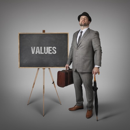ethics and morals: Values text on  blackboard with businessman holding umbrella and suitcase