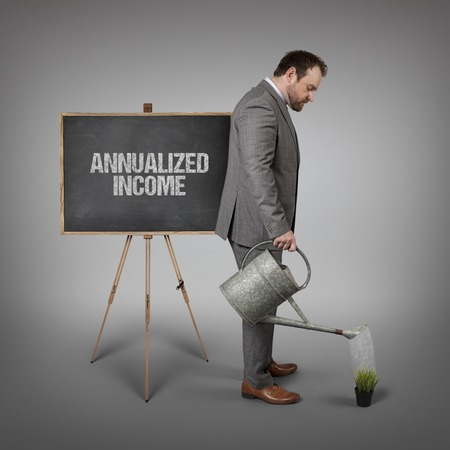 watering plant: Annualized income text on  blackboard with businessman watering plant