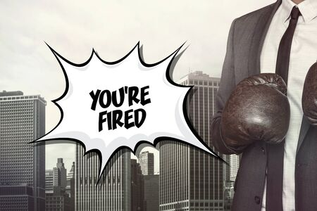 you are fired: Youre fired text on speech bubble with businessman wearing boxing gloves