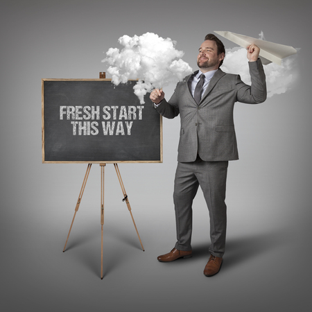 fresh start: Fresh start this way text on blackboard with businessman and paper plane