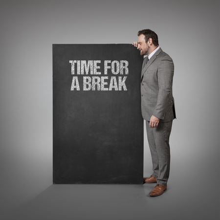 discontinuity: Time for a break text on blackboard with businessman standing side