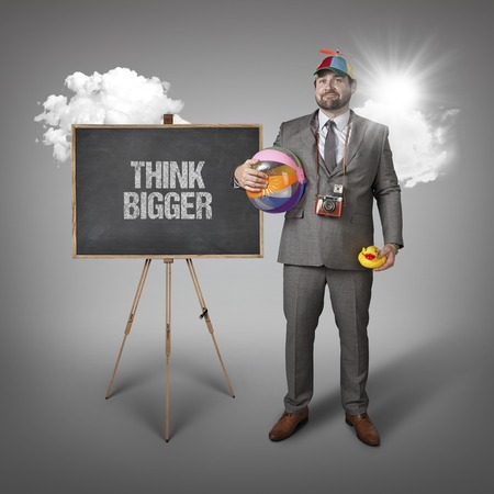 broader: Think bigger text with holiday gear businessman and blackboard with text Stock Photo