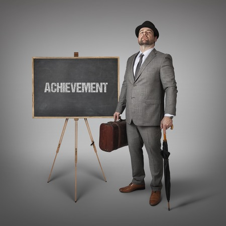 attainment: Achievement text on  blackboard with businessman holding umbrella and suitcase Stock Photo