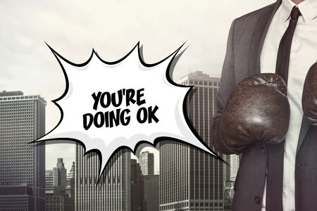 endorsement: Youre doing ok text on speech bubble with businessman wearing boxing gloves