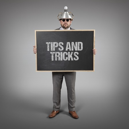 science tips: Tips and tricks text on blackboard with science businessman holding blackboard sign Stock Photo
