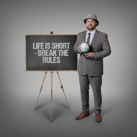 break the rules: Life is short - break the rules text on blackboard with businessman holding globe in hands