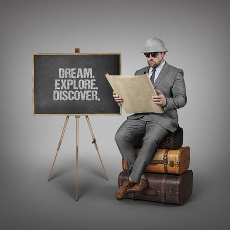 ascertain: Dream. Explore. Discover. text on  blackboard with explorer businessman sitting on suitcases