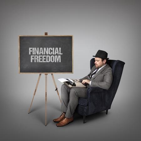 key to freedom: Financial freedom text on  blackboard with businessman and key
