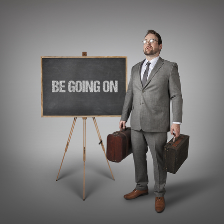 uninterrupted: Be going on text on  blackboard with businessman carrying suitcases Stock Photo