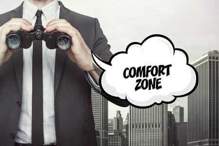 contented: Comfort zone text on speech bubble with businessman holding binoculars on city background