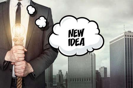 new idea: New idea text on speech bubble with businessman holding lamp