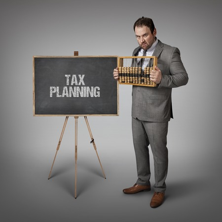 excise: Tax planning text on blackboard with businessman and abacus