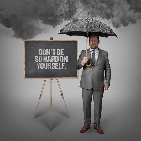 relentless: Dont be so hard on yourself text on blackboard with businessman holding umbrella