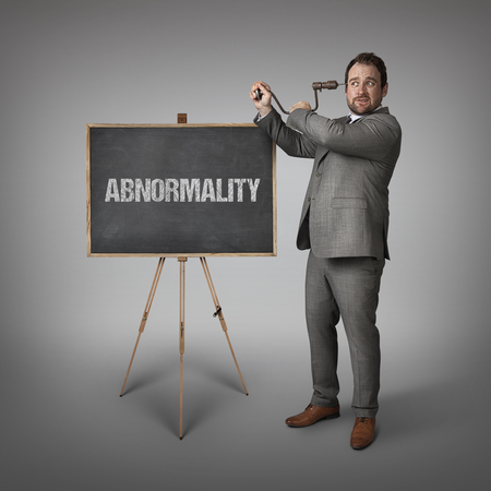 odd jobs: Abnormality text on blackboard with businessman drilling his head Stock Photo