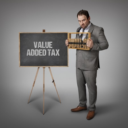 are added: Value added tax text on blackboard with businessman and abacus Stock Photo