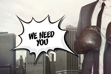 necessity: We need you text on speech bubble with businessman wearing boxing gloves