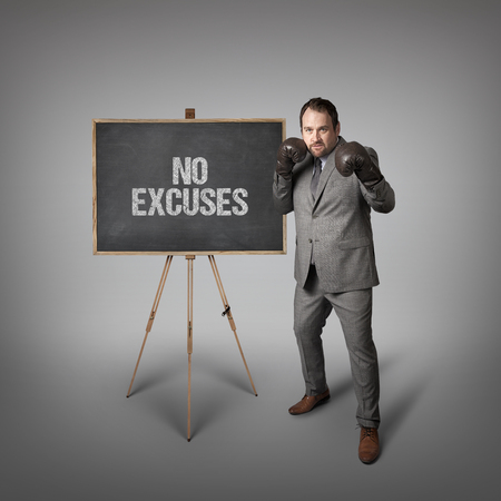 reasons: No excuses text on  blackboard with businessman wearing boxing gloves