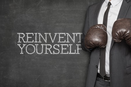 formulate: Reinvent yourself on blackboard with businessman wearing boxing gloves