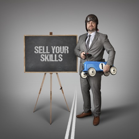 competences: Sell your skills text on blackboard with businessman and toy car