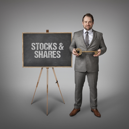 accumulations: Stocks and Shares text on  blackboard with businessman and key Stock Photo