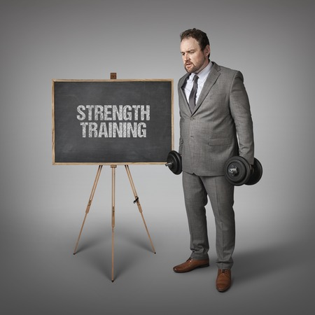 heaviness: Strength training text on blackboard with businesssman holding weights