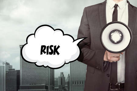 acquire: Risk text on speech bubble with businessman holding megaphone