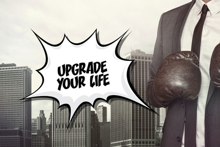 enhancement: Upgrade your life text on speech bubble with businessman wearing boxing gloves Stock Photo