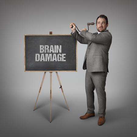 brain damage: Brain damage text on blackboard with businessman drilling his head