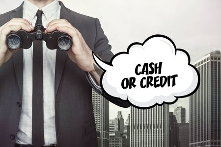 Cash or Credit text on  blackboard with businessman and key