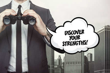 ability to speak: Discover your strenghts text on speech bubble with businessman holding binoculars on city background