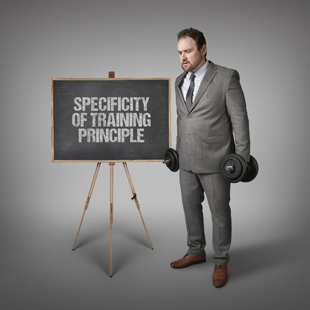specificity: Specificity of Training Principle text on blackboard with businesssman holding weights Stock Photo