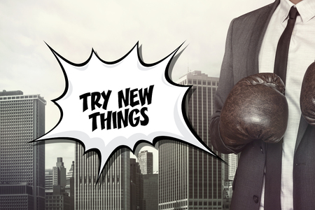 undertake: Try new things text on speech bubble with businessman wearing boxing gloves