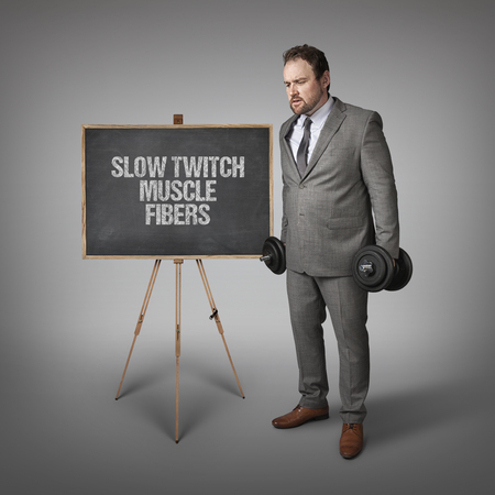 twitch: Slow twitch muscle fibers text on blackboard with businesssman holding weights Stock Photo