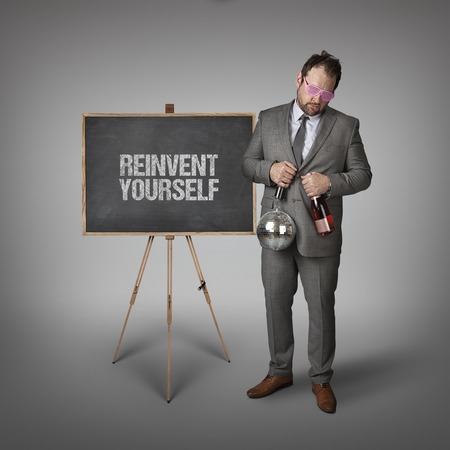 reconstruct: Reinvent yourself text on blackboard with businessman and key