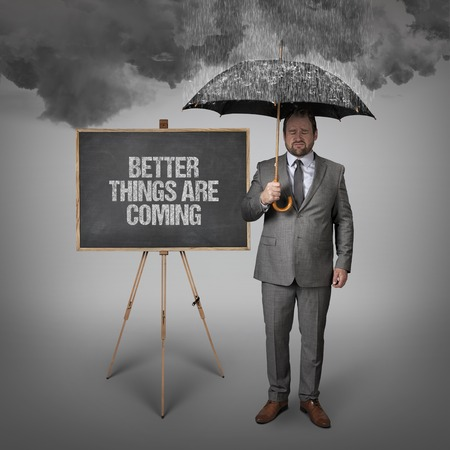 forthcoming: Better things are coming text on blackboard with businessman holding umbrella