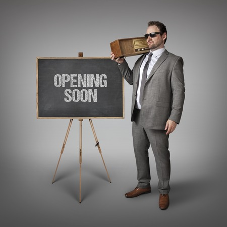 presently: Opening soon text on blackboard with businessman holding radio Stock Photo