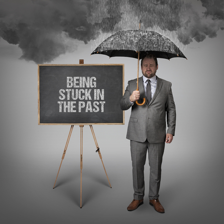 unwillingness: Being stuck in the past text on blackboard with businessman holding umbrella Stock Photo