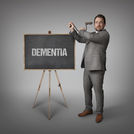 foolishness: Dementia text on blackboard with businessman drilling his head Stock Photo