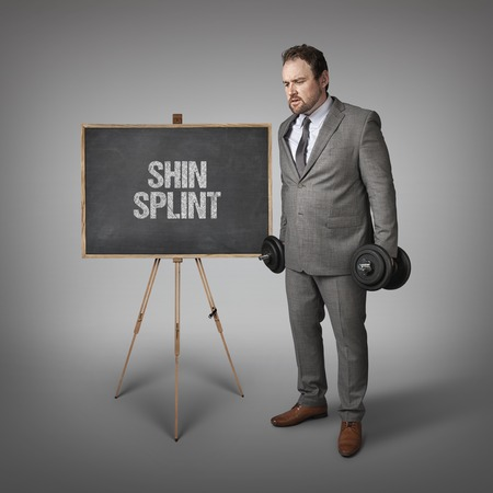 splint: Shin splint text on blackboard with businesssman holding weights Foto de archivo