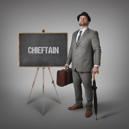 chieftain: Chieftain text on  blackboard with businessman holding umbrella and suitcase