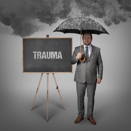 rehabilitated people: Trauma text on blackboard with businessman holding umbrella