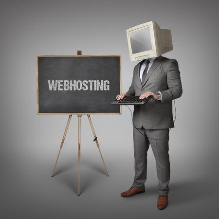 webhosting: Webhosting text on blackboard and computer monitor on businessman head