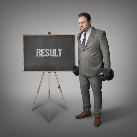 outcomes: Result text on blackboard with businesssman holding weights Stock Photo